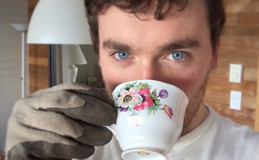 Blue-eyed man with work glove and china teacup